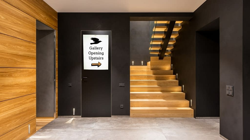 """the lobby of a fancy looking gallery with black walls and light wood staircase. a sign on the wall reads """"gallery opening upstairs"""" with an arrow pointing towards the staircase"""
