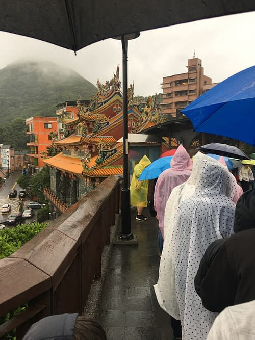 waiting in line with a bunch of poncho-clad tourists, under cloudy skies, in front of a temple