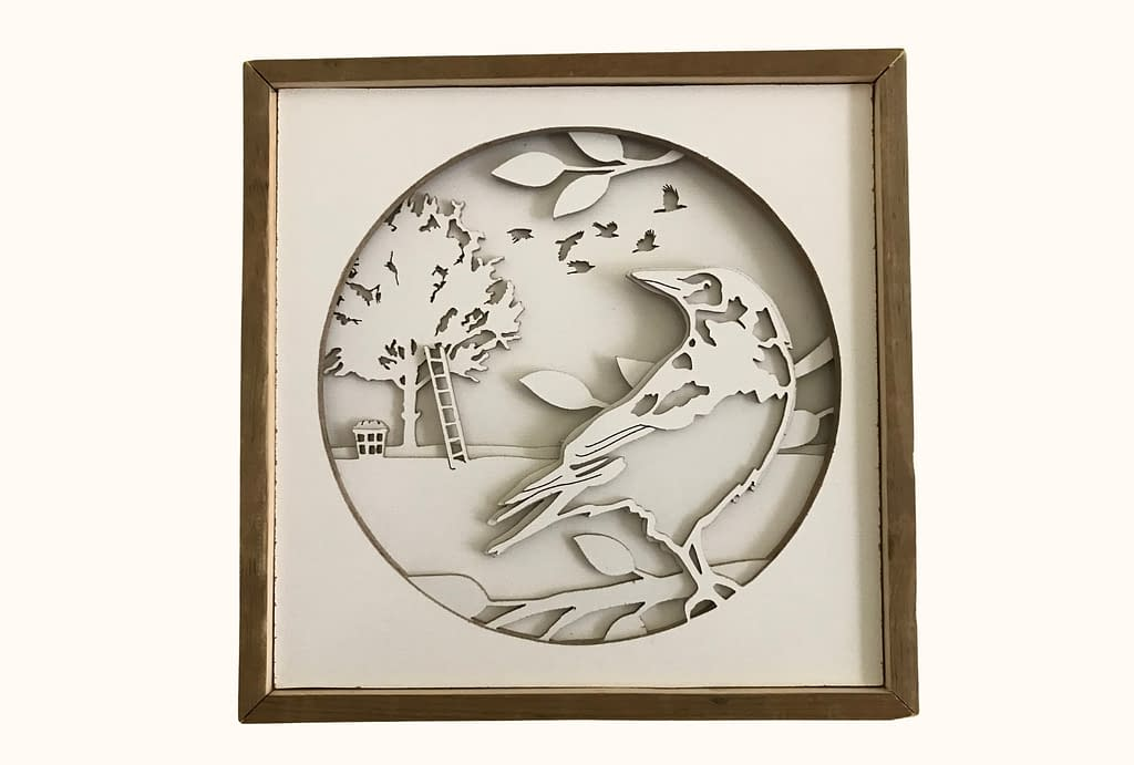 A crow shadowbox cut from layers of hardboard. In the foreground, a crow is perched in the branches. In the background, a flock of crows flies through the sky and a ladder leans up against an apple tree with a basket of apples at the bottom.