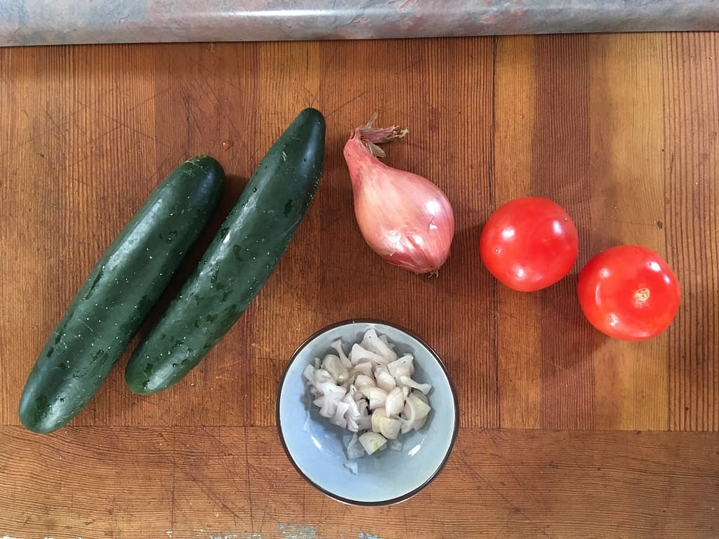 whole cucumbers, shallots, and tomatoes on a wooden cutting board, plus a small bowl of chopped shallots
