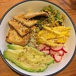 bowl full of sauteed tofu and cabbage, fresh mango and avocado, and pickled radish on top of rice