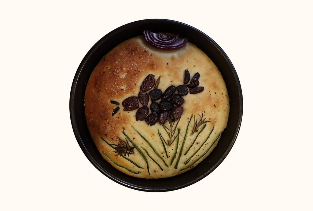 A circular loaf of focaccia inside a pan sitting on a shelf. A crow made of olives flies across the center. A red-onion sun and chive grass round out the composition.