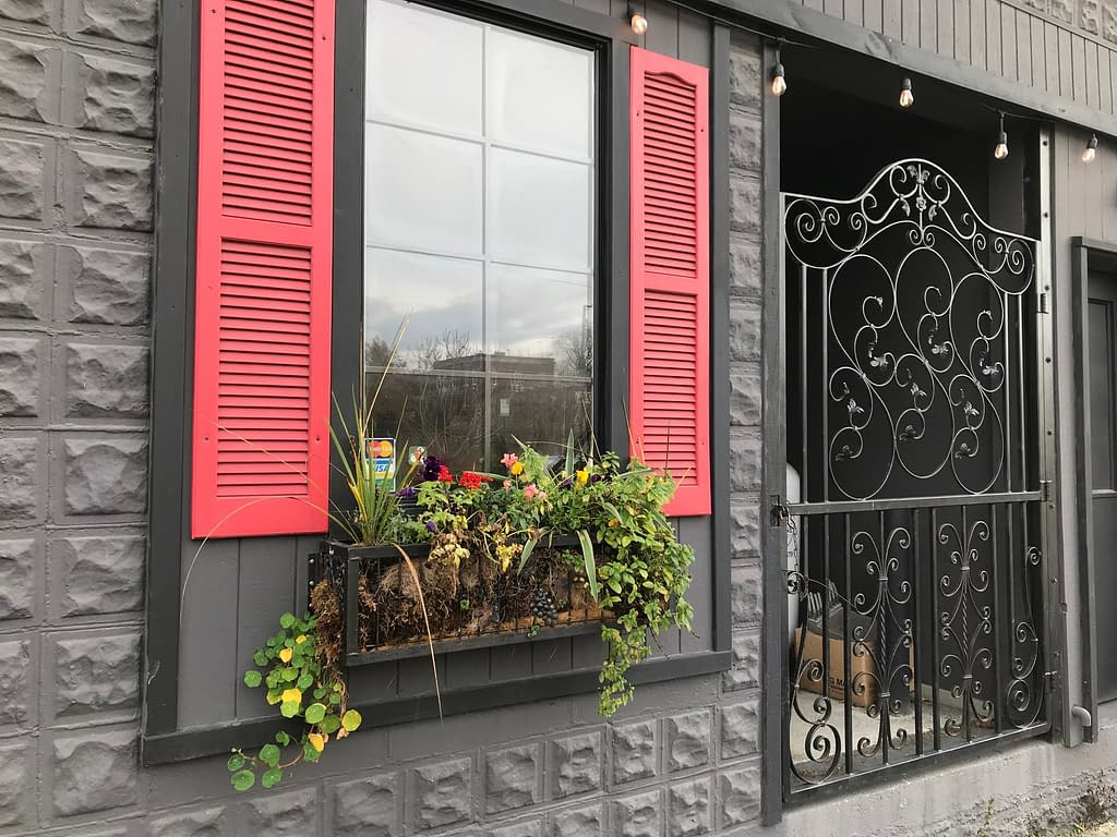 a window in a grey wall framed by red shutters with a flower box underneath and next to an iron gate