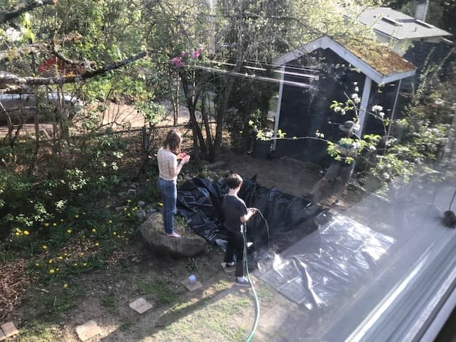 a boy fills the pond, which is draped in a black liner, with water from a hose. his sister looks on, filming the scene on her phone.