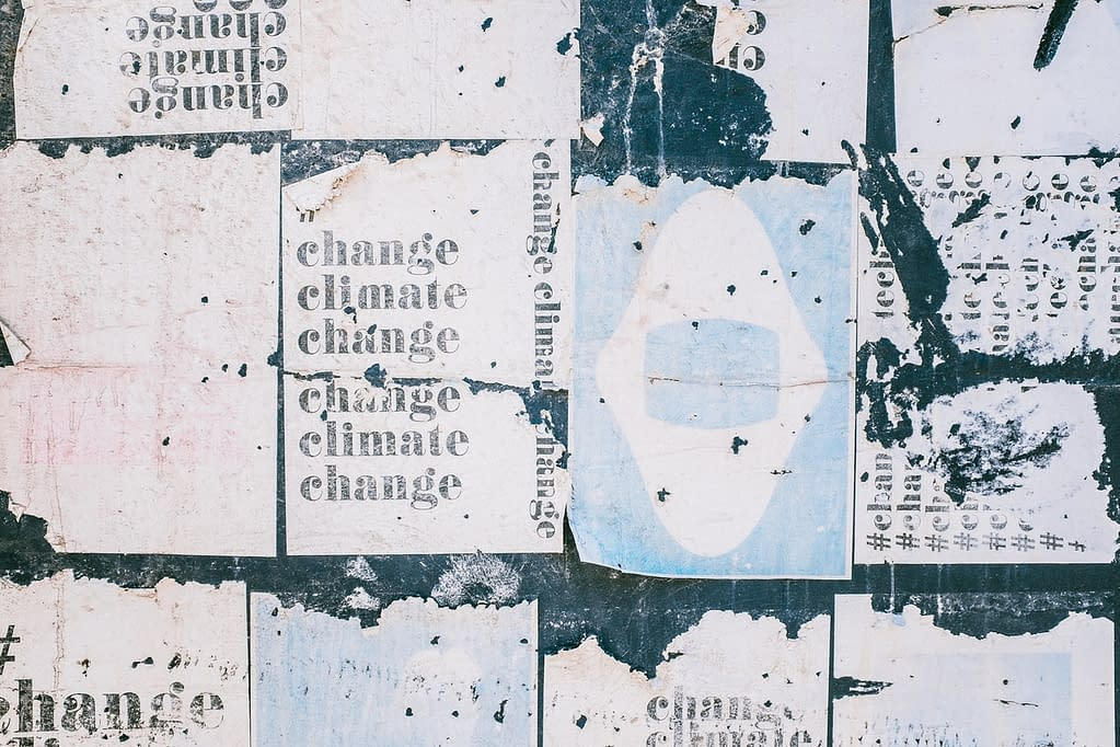 "posters plastered on a wall saying ""change climate change"""