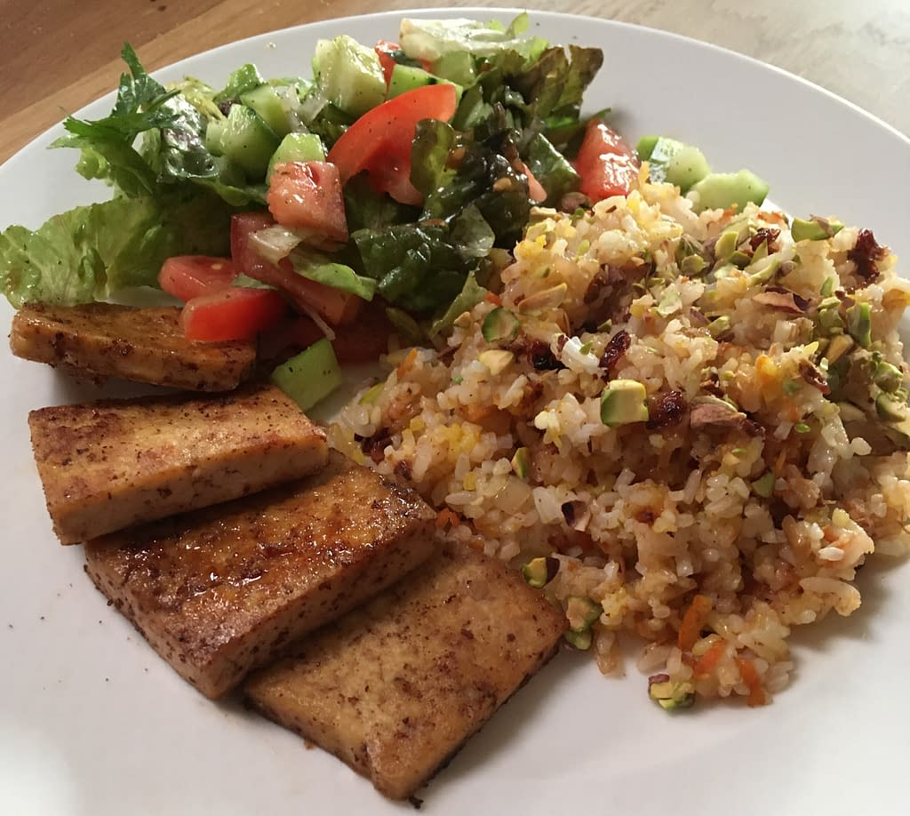 tofu cutlets with barberry rice and a green salad with cucumber and tomatoes