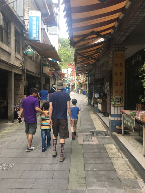 Four people walking through a narrow alleyway with small shops on either side.