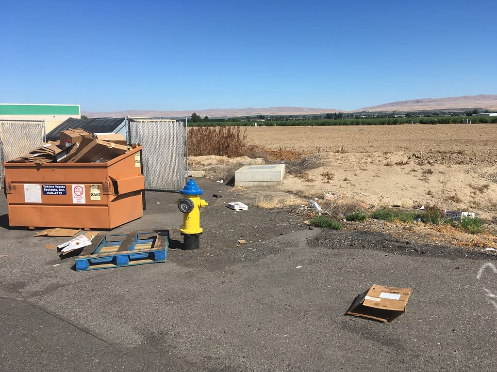 Orange Dumpster overflowing with cardboard boxes next to a discarded wooden pallet and a bright yellow fire hydrant, with brown flat land behind them, and a stripe of green farmland and dusty brown hills in the distance.
