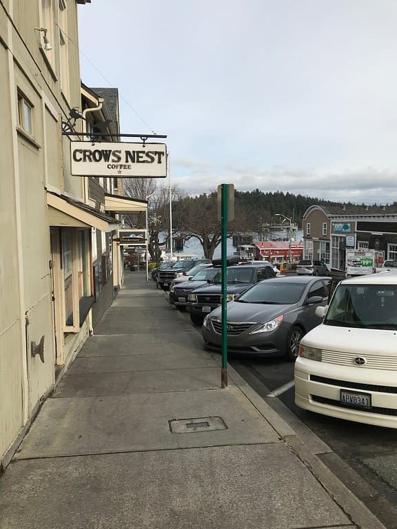 "line of shops with the ferry dock in the distance. Sign reads, ""Crows Nest coffee"""