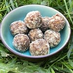 a bowl full of date tahini energy bites in the grass