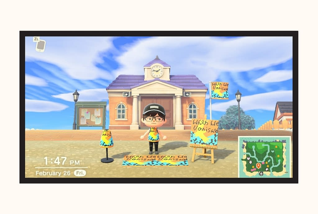 An avatar of a boy in Animal Crossing stands in front of town hall displaying the When We Vanished pixel art that was created to mimic the cover. It is being modeled on the flag outside the building, a canvas on an easel, a rug on the ground, and on a T-shirt the character is wearing.