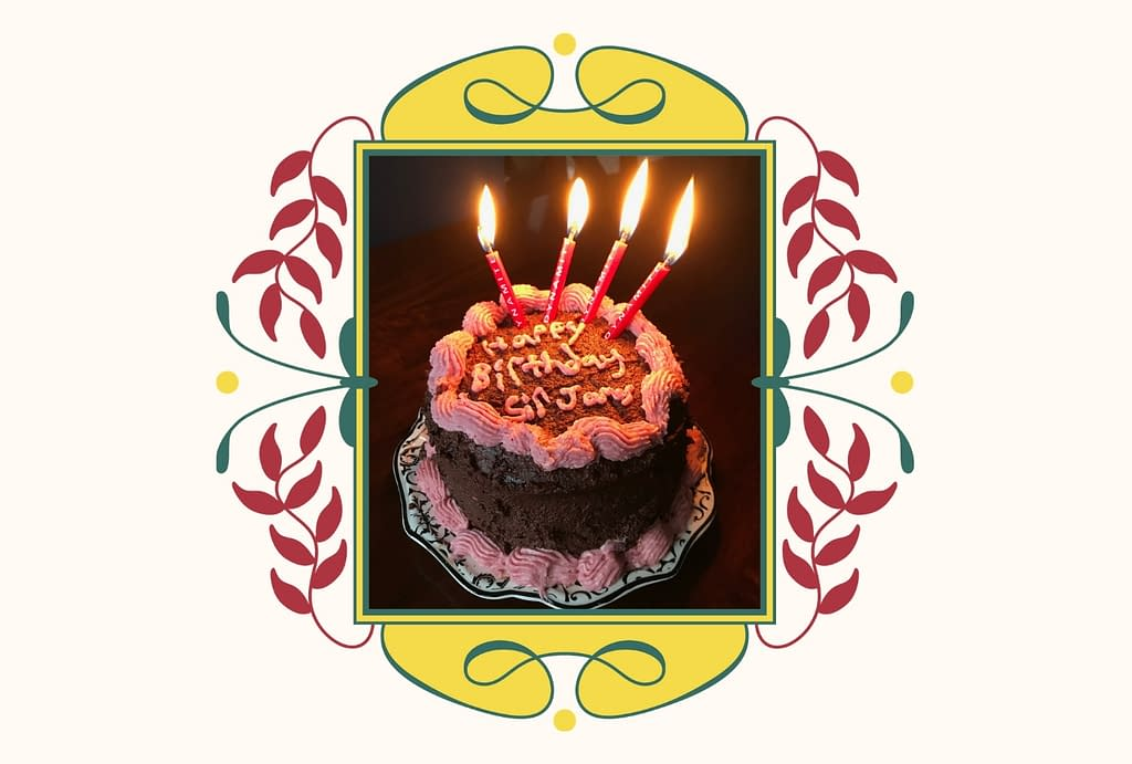 """A photograph of a layer cake covered in chocolate icing with pink frosting details. The cake inscription reads, """"Happy birthday, sir james."""" there are four red candles at the top that say """"dynamite."""""""