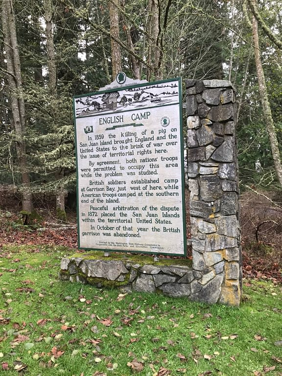 "Sign reads, ""English Camp. In 1859 the killing of a pig on San Juan Island brough England and the United States to the brink of war over the issue of territorial rights here. By agreement, both nations' troops were permitted to occupy this area while the problem was studied. British soldiers established camp at Garrison Bay, just west of here, while American troops camped at the southern end of the island. Peaceful arbitration of the dispute in 1872 placed the San Juan Islands within the territorial United States. In October of that year the British garrison was abandoned."""
