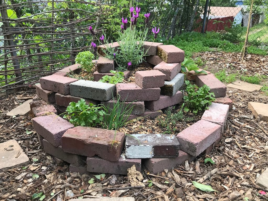 side view of a spiral garden bed made with bricks